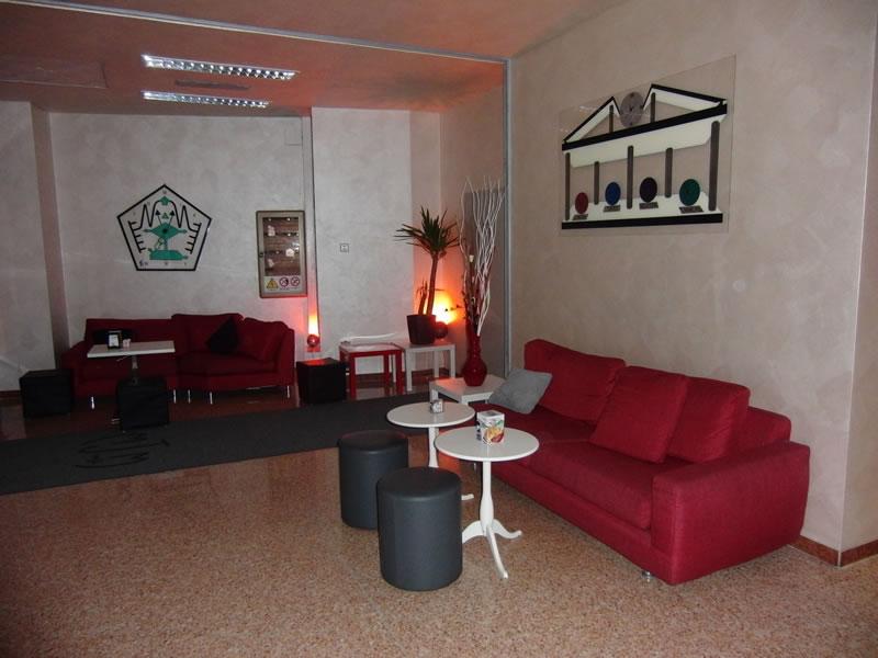 Foto saletta con divanetti rossi scattati presso il Bar Tabacchi Tavola Calda MJM a Milano