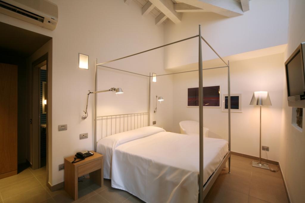 Letto e camera da letto arredata presso l'Hotel San Rocco a Bergamo