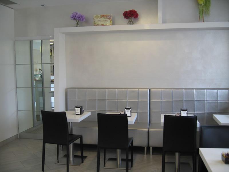 Foto angolo ristoro con sedie e divanetto grigio presso la Pasticceria Panificio Caffetteria La Meta a Lazzate, Monza Brianza