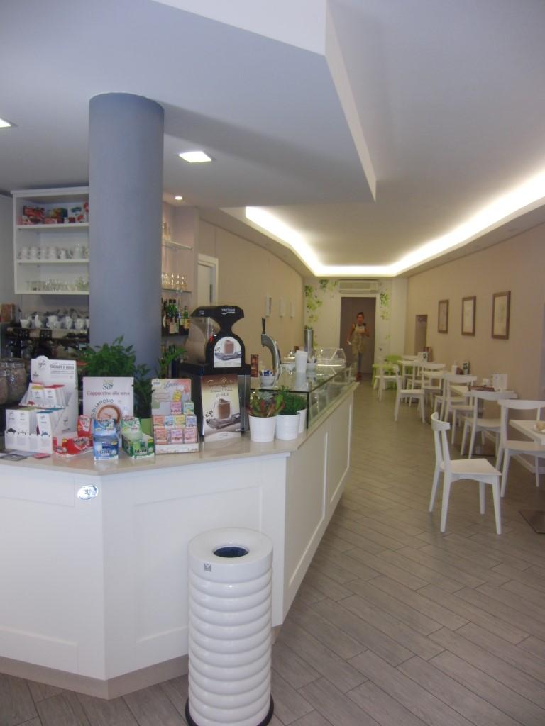 """Foto con angolo bar e vista del corridoio arredato con sedie e tavolini presso il Bar Tavola Fredda """"CACAO"""" a Bergamo"""