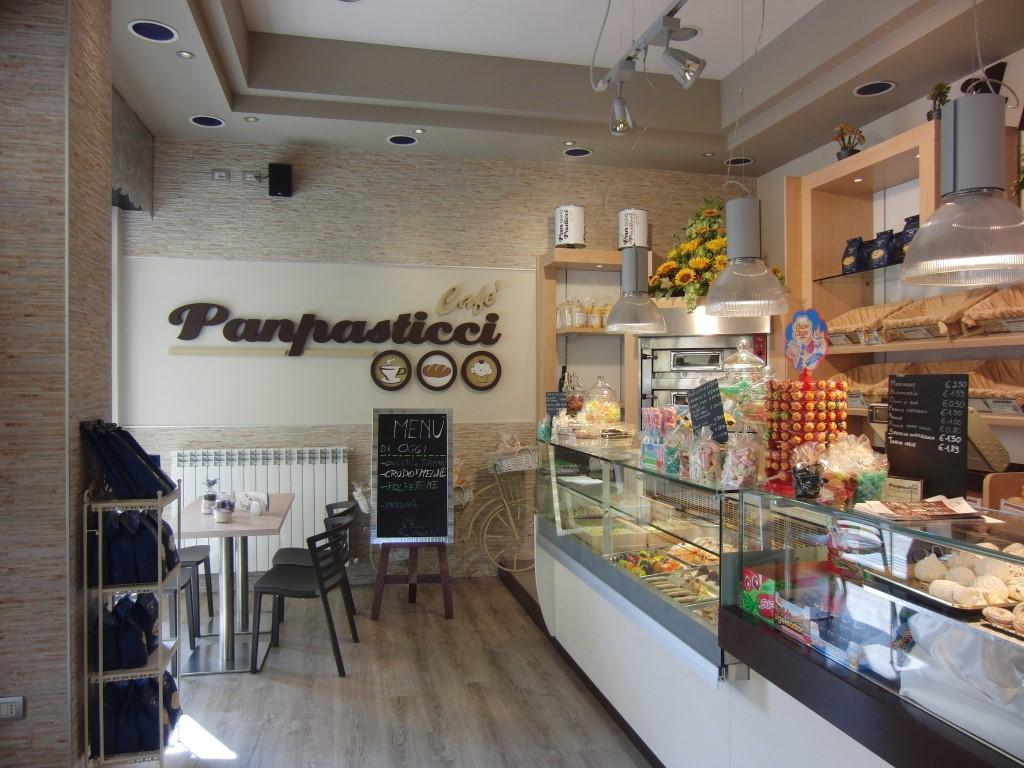 """Foto del bancone principale con vista sul logo nella parete del Panificio Bar """"Panpasticci Cafè"""" a Dalmine, Bergamo"""