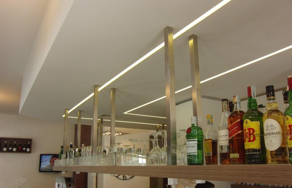 Particolare della mensola con alcoolici ed illuminazione sulla parete a led, presso il Bar Tabacchi Barranca a Milano