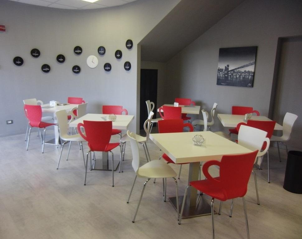 Saletta bar con tavolini e sedie bianche e rosse presso il Cogal Caffè ad Albino in Provincia di Bergamo
