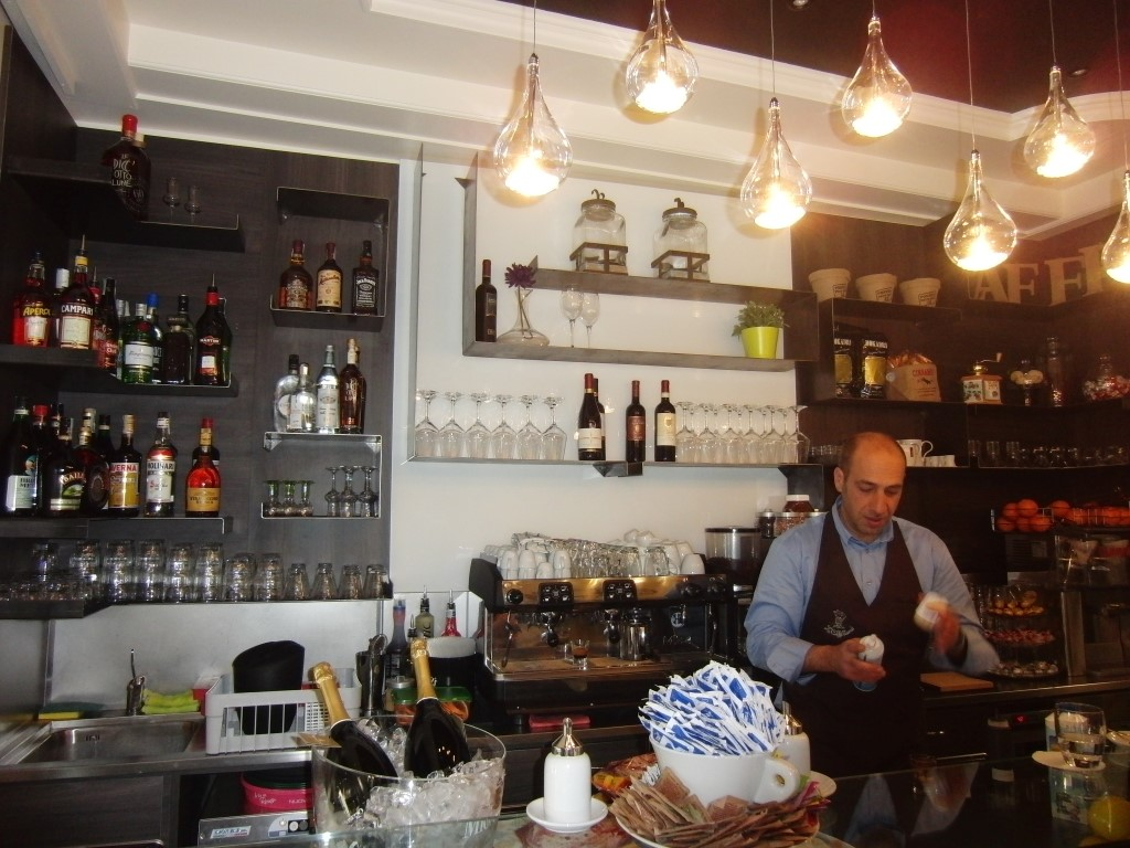 """Foto del titolare del Bar tavola fredda """"La Caffettiera"""" a Pavia, al lavoro dietro il banco bar"""
