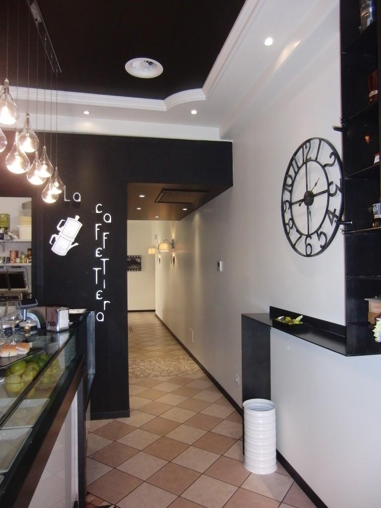 """Foto dell'ingresso con orologio e logo del locale presso il Bar tavola fredda """"La Caffettiera"""" a Pavia"""