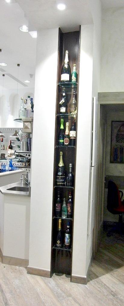 Foto di una colonna del Wine Bar Cocktails, Cafè Olimpia a Milano, recuperata con l'inserimento di una zona per le bottiglie