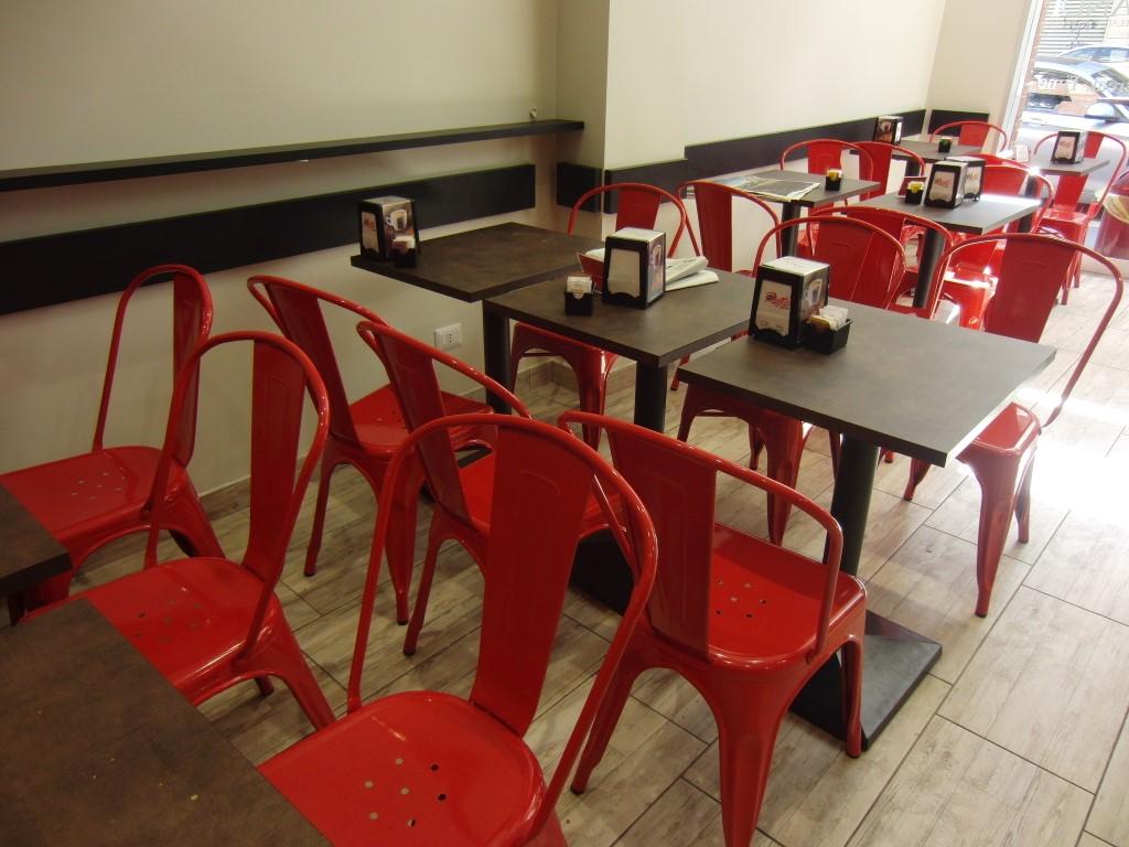 Foto della sala interna con tavoli nere e sedie rosse presso la Gelateria Caffetteria Rembrandt a Milano
