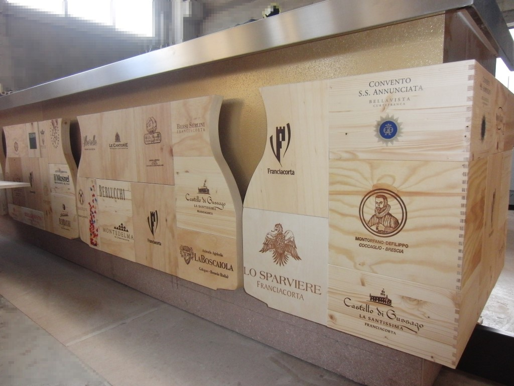 Foto dei pannelli del banco bar realizzati con le cassette dei vini al Ristorante Wine Gate 11 presso l'Aeroporto di Orio al Serio