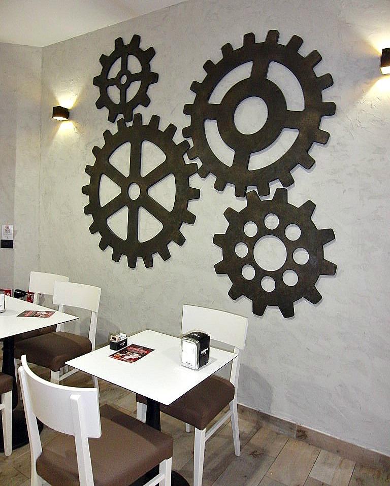 Particolare della parete con ingranaggi appesi al muro presso la Pasticceria Caffetteria i 4 Mastri a Milano