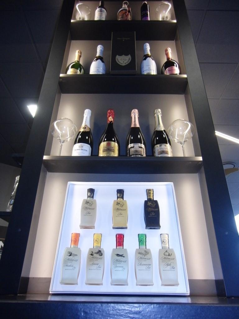 Foto della colonna espositiva illuminata a led con varie bottiglie presso il Perlage Coffee & Lounge Bar a Bonate Sopra