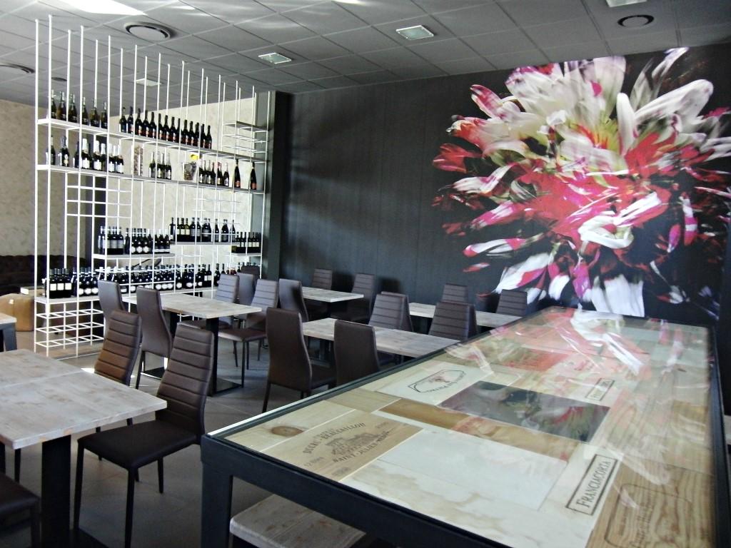 Foto dei tavoli con vista sull'espositore dei vini e tavolo realizzato con le cassette in legno dei vini, presso Perlage Coffee & Lounge Bar a Bonate Sopra
