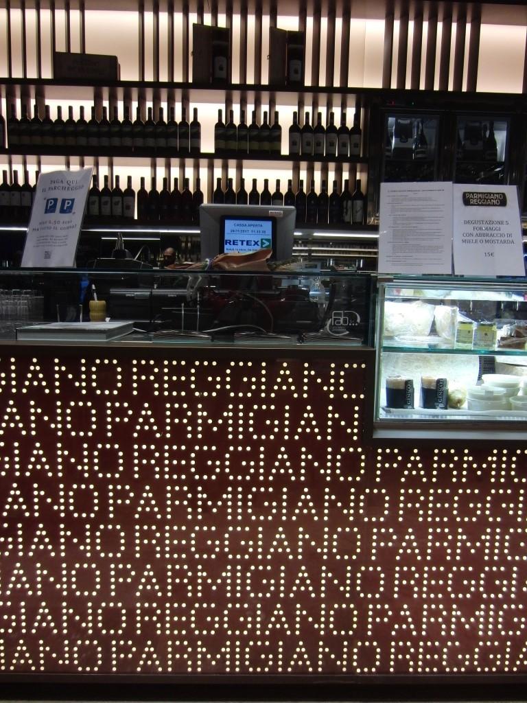 Bancone illuminato presso lo stand del consorzio del parmigiano reggiano a eataly nella città di bologna